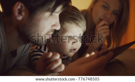 Closeup of Happy young family lying in bed at home while little boy learning to play digital tablet computer before sleeping time #776748505