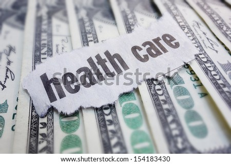 Closeup of health care newspaper headline, on cash