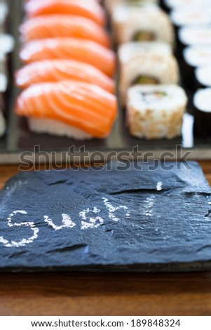 Closeup of healthy freshly prepared sushi rolls with decorative label stone with text in chalk