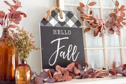 Closeup of Hello Fall sign and rust colored leaves on a mantel decorated for autumn