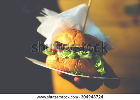 Closeup of home made burger in hand. Toned picture
