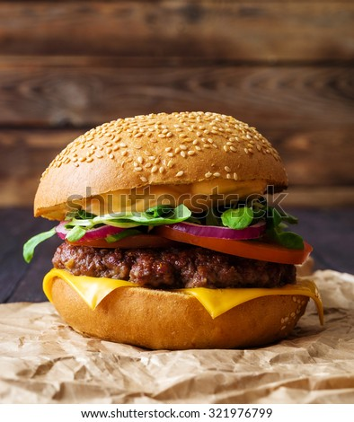Closeup of home made burger on wooden background.