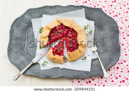 Closeup of homemade red currants galette on a serving plate placed on a natural wood surface covered with red white cloth