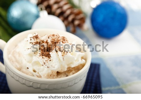 Closeup of hot chocolate cocoa with whipped cream and shaved chocolate, the perfect winter comfort food set against a blue background