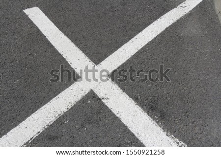 closeup of huge white painted cross diagonals marking prohibited area on road surface zone #1550921258