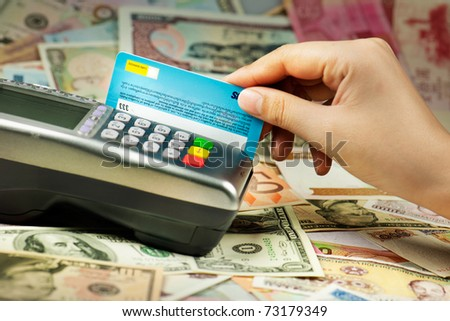 Closeup of human hand putting credit card into payment machine