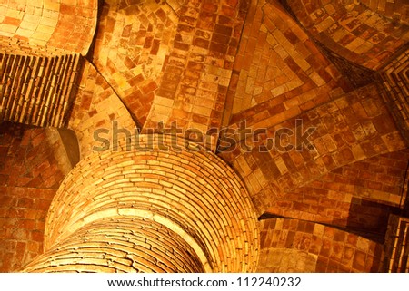 Closeup of illuminated top of a column supporting radiating brick arches