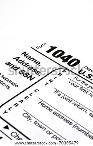 Closeup of IRS form 1040 on white background with ink pen and coffee. - stock photo