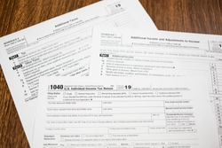 Closeup of IRS 2019 Tax Return form 1040 on wooden table. Taxation reminder.
