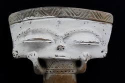 Closeup of isolated abstract inca clay figure with rectangular head and white face from Peru. Black background.
