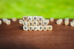 Closeup of isolated dices on a table showing the words make, learn, repeat infront of a saturated background