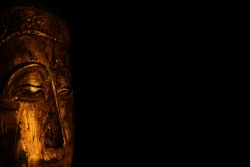 Closeup of isolated illuminated golden Buddha face mask on black blank background with copy space for text (focus on eye left)