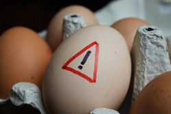 Closeup of isolated raw brown eggs in carton box with warning sign - salmonella infection risk and cholesterol consumption