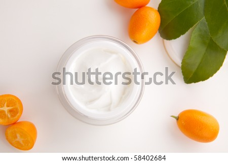 Closeup of jar of moisturizing face cream and fresh citrus