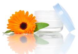 Closeup of jar of moisturizing face cream and fresh marigold flower isolated on white background