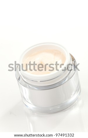 Closeup of jar of moisturizing face cream surrounded by pink tulip flowers