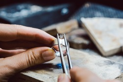 Closeup of Jeweler setting a precious stone with pincers on a ring
