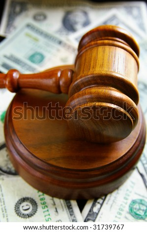closeup of judges court gavel, over american money