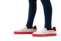 Closeup of kid wearing adult shoes on white background. Concept of maturity and growing up.