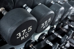 Closeup of 37.5 kilogram dumbbells placed on a dumbbell rack at the gym. Weight training equipment.