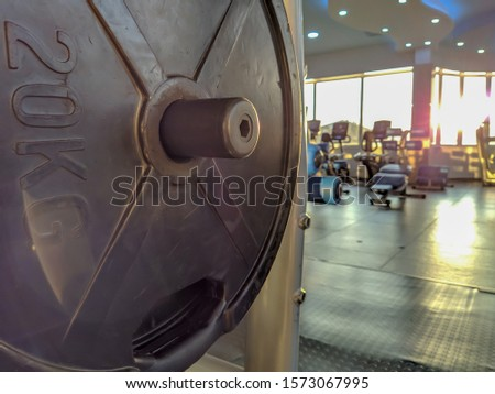 Closeup of 20 kilogram weight metal steel and modern gym equipment around on a sunny day during an everyday recreational workout