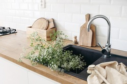 Closeup of kitchen interior. White brick wall, metro tiles, wooden countertops with chopping boards. Cow parsley plants in black sink. Modern scandinavian design. Home staging, cleaning concept.