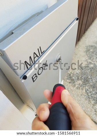 Closeup of lady using screwdriver to fix up her mail box. Household fixing tools concept.