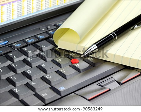 Closeup of laptop keyboard with paper for notes and pen