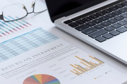 Closeup of laptop or notebook computer and financial reports with colorful charts, graphs and diagrams for business performace and return on investment, ROI, analysis