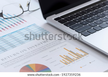 Closeup of laptop or notebook computer and financial reports with colorful charts, graphs and diagrams for business performace and return on investment, ROI, analysis Stock photo ©
