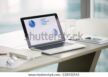Closeup of laptop with graphs on screen on white modern office desk, preparation for formal meeting of the board of directors, effective management. Office interior. Business success concept. Close up