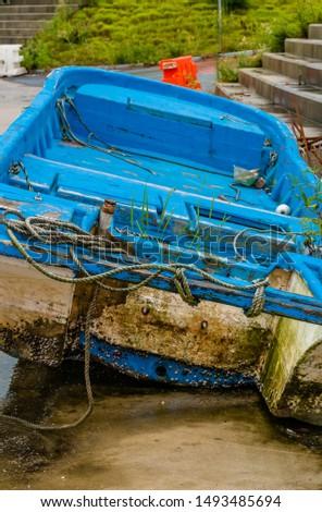 Closeup of large large blue fishing boat dry docked on concrete pier on rainy morning.