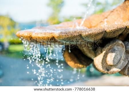 Closeup of light splashing water in sunny stone fountain in European village park in summer