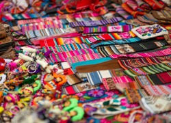 Closeup of light striped handbags with weaves, colorful bracelets and different key chains on the souvenir store in Peru