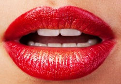 Closeup of lips with red lipstick and gold