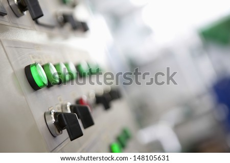 Closeup Of Lit Lights And Control Dials On Manufacturing Machinery