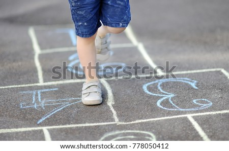 Closeup of little boy's legs and hopscotch drawn on asphalt. Child playing hopscotch game on playground outdoors on a sunny day. Summer activities for children. - Shutterstock ID 778050412