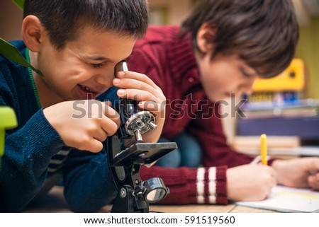 Closeup of little boy using microscope on biology lesson #591519560