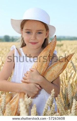 Closeup of little girl holding bread in wheat field - stock photo