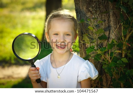 Closeup of little girl with magnifying glass standing near the tree stem outdoors
