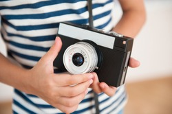 closeup of little kid wearing striped shirt with hands holding vintage camera