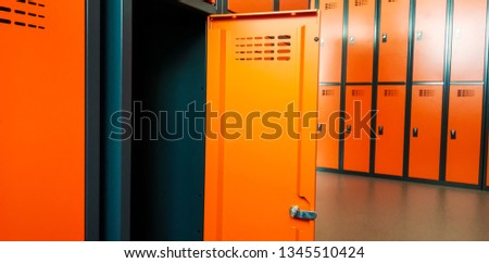 Closeup of locker room situated in work place. Orange lockers, storage for workers. #1345510424
