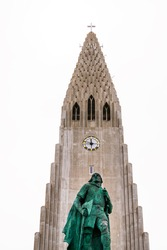 Closeup of Lutheran church of Hallgrimskirkja in Reykjavik, Iceland with bronze statue of Leif Erikson in downtown capital city