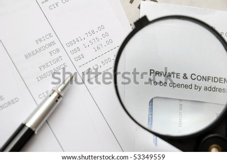 Closeup of magnifying glass on security related text on letter with pen on money related documents in background. For privacy and confidentiality, security and protection concepts.
