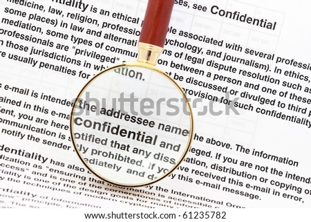 Closeup of magnifying glass on security related text on letter with sensitive business documents in background. For privacy and confidentiality, security and protection concepts.