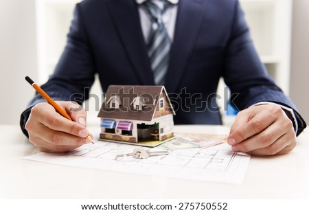 Closeup of male architect drawing heating system plan of customer house in the office. Real estate value and cost concept.  Shallow depth of field.