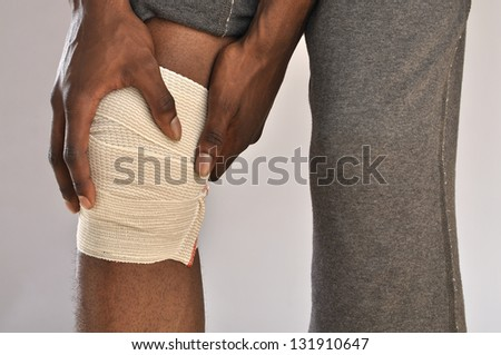 Closeup of male athlete clutching knee wrapped in sports bandage on grey background