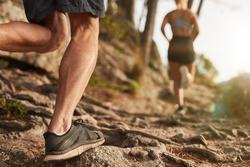 Closeup of male feet run through rocky terrain. Cross country running with focus on runner's legs.