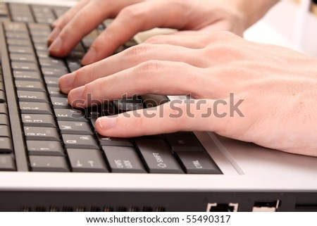 Closeup of male fingers typing a document on the black laptop