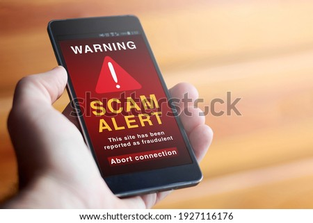 """Closeup of male hand holding modern mobile phone with red screen and warning icon with the text """"SCAM ALERT: This site has been reported as fraudulent. Abort connection"""". Concept of internet security."""